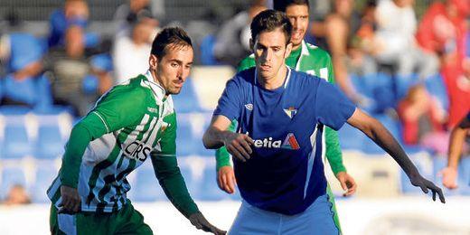 El mediapunta azulino Rubén Cruz busca el esférico ante la presión del defensa central verdiblanco Manu Herrera.