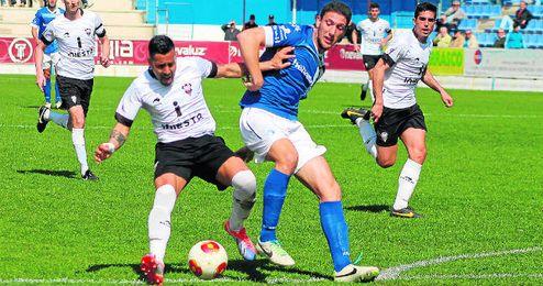 El defensa ecijano Manzano presiona a un rival albaceteño durante el partido.