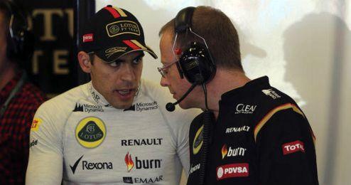 El piloto de Lotus, Pastor Maldonado, dialoga con uno de sus mecánicos.
