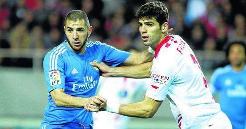El sevillista Federico Fazio pugna con el madridista Karim Benzema durante el partido de Liga en el Sánchez Pizjuán.