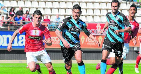El lateral zurdo Álex Martínez sale al paso de otro bético que buscó minutos lejos del Villamarín, el mediapunta Sergio Rodríguez, durante el Murcia-Lugo.