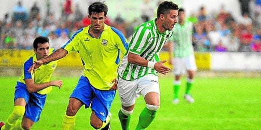 En la imagen, el lateral amarillo Juan José corre detrás de Steinhöfer, en el amistoso del Coria ante el Betis.