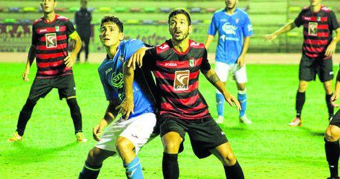 El lateral izquierdo rojinegro Salvi pugna con el medio isleño Chapi, en un lance del encuentro jugado ayer.