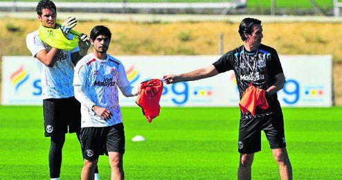 Emery le da un peto a Banega en la sesión de ayer, en la que trabajaron con el balón de la Copa como novedad.
