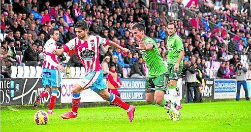 El capitán del Lugo conduce el balón ante la mirada de un futbolista del Racing.