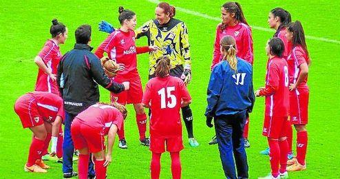 Cori bromea con sus compañeras sobre el césped de Zubieta, y en presencia de su entrenador Fran Licera.