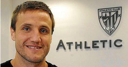 Carlos Gurpegui con el escudo del Athletic Club de fondo