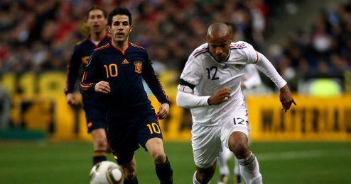 Fábregas y Henry disputan un balón en un partido internacional
