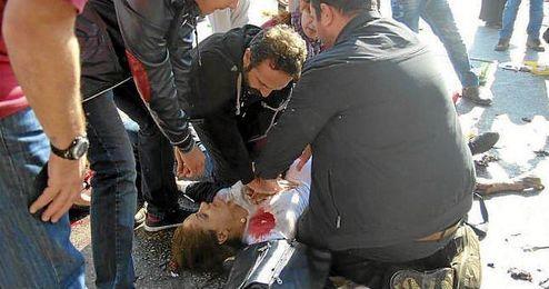 Varias personas intentan reanimar a una de las víctimas.