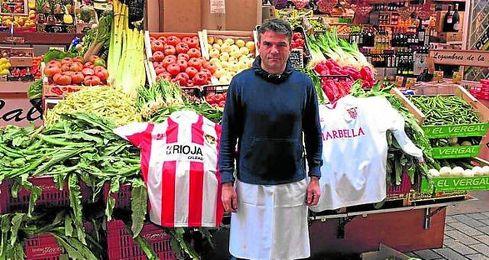 Pedro posa para ESTADIO Deportivo frente a su frutería en el centro de Logroño, donde guarda sus camisetas del Logroñés y el Sevilla.