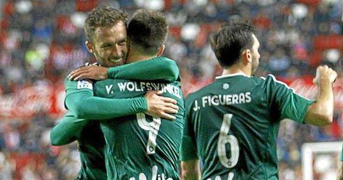 Pezzella se abraza a Van Wolfswinkel tras su gol.