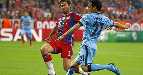 El recién renovado Xabi Alonso en una disputa de un balón con David Silva.