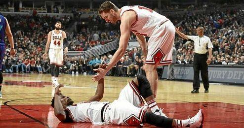 Gasol ayuda a levantarse a Butler en un partido.