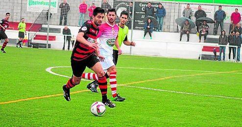 El minero José Rodríguez conduce el balón ante la mirada del rojillo Romero durante el duelo jugado ayer.