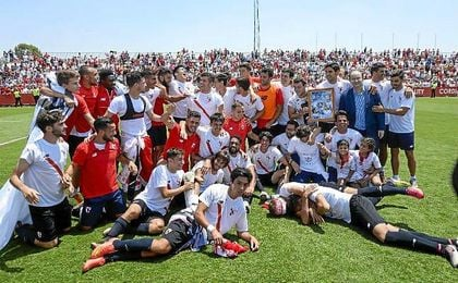 La plantilla del Sevilla Atlético celebra el ascenso sobre el césped.