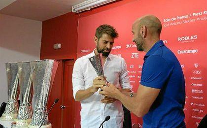 Monchi hace entrega a Coke de una réplica de la tercera Europa League ganada por el Sevilla.