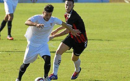 Giráldez conduce el esférico ante la presión de Bucarat en el Sevilla C-Cabecense.