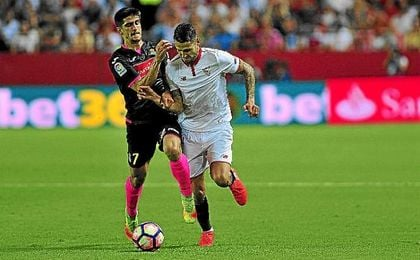 Vitolo conduce el balón en carrera ante un rival.