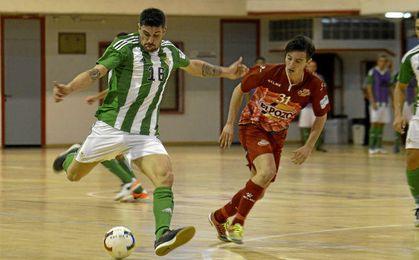 Juanillo golpea el balón ante la mirada de un rival.