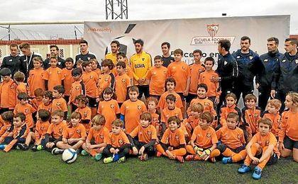 Gago y Pablo Pérez, en el centro, se fotografiaron con los niños de la Escuela de Fútbol Antonio Puerta.