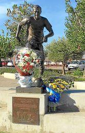 Imagen de los ramos de flores bajo la estatua de Antonio Puerta.