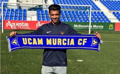 Iván posando con la bufanda del UCAM Murcia. UCAMM.