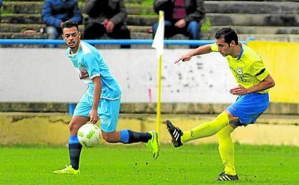 El jugador del Coria, Curro, centra ante la mirada del futbolista de la Lebrijana, Braganza, en un lance del encuentro de ayer.