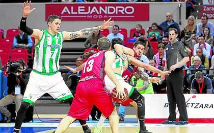 El ala-pívot del Tecnyconta Zaragoza Simon Pursl intenta pasar ante los jugadores del Real Betis Bostjan Nachbar y Tomeu Rico.