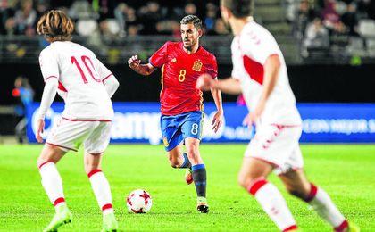 Ceballos conduce el balón ante la oposición de dos jugadores de Dinamarca.