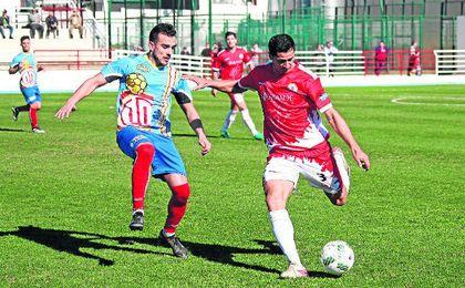 Jesús Blanco (izquierda) presiona a un rival del San Roque en un lance del encuentro disputado en el Manolo Mesa en la presente temporada.