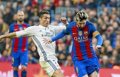 Ronaldo y Messi disputando un balón en el Clásico.