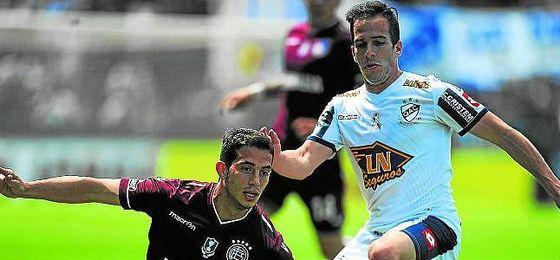 Iván Marcone se lanza al suelo para despejar un balón ante un rival esta campaña con Lanús.
