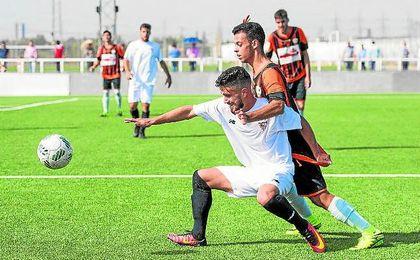 Chuma puja por un balón con Braganza en el Sevilla C - Lebrijana de la pasada temporada.