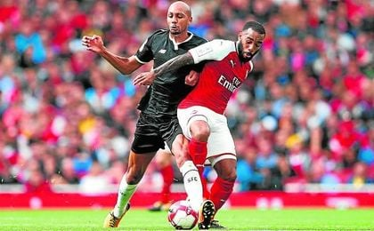 N´Zonzi pugna con Lacazette durante el choque de ayer en la Emirates Cup.