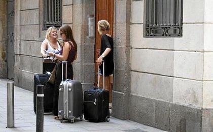 Tres turistas esperan delante de un piso de alquiler en Barcelona.