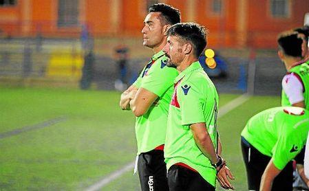 Fran García, en segundo plano, entrenador del Atlético Dos Hermanas, atento a su equipo.