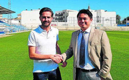David Páez, nuevo entrenador del Écija, estrecha la mano de Yung Gon Park, presidente azulino.