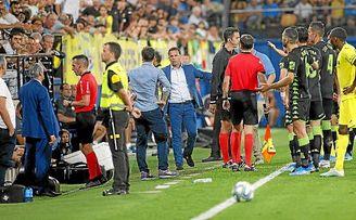 Los jugadores del Betis y del Villarreal esperan la decisión del colegiado, que mira el monitor del VAR.